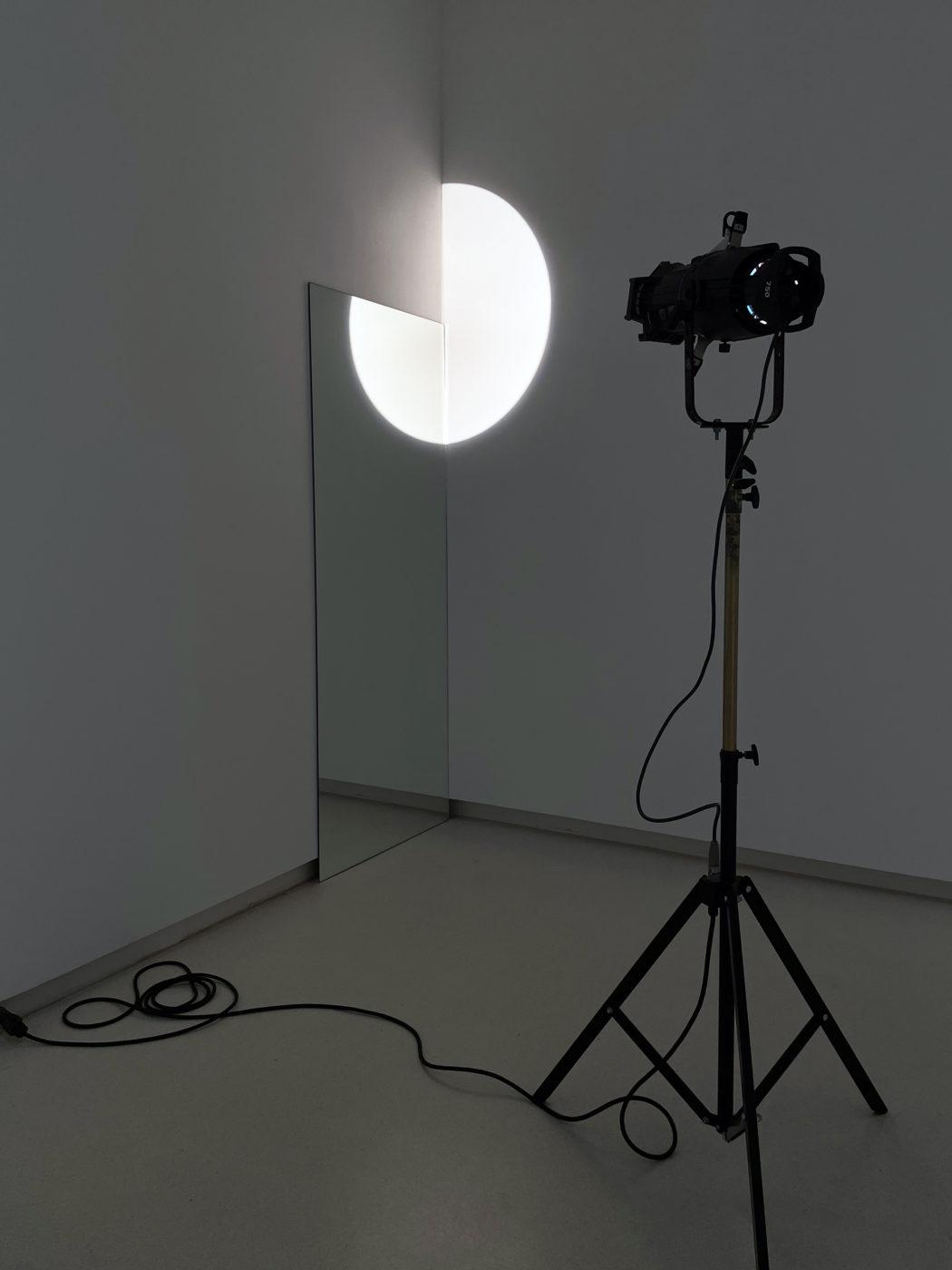 Escultura Olafur Eliasson Mirror door (performer) 2008 foco trípode y espejo que completa un círculo proyectado en la pared y reflejado en el espejo